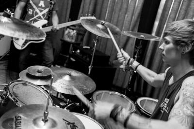 een drummer repeteert op zijn drumstel