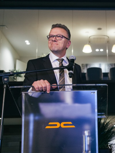 de eigenaar van Dicar kijkt tevreden in zijn nieuw gebouw tijdens een toespraak