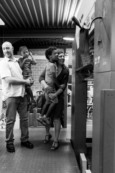 bezoekers kijken gefascineerd naar de drukpers