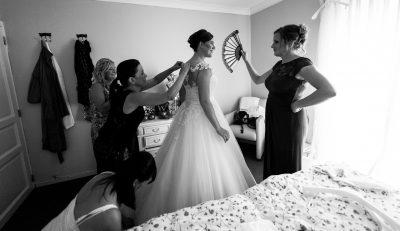 de bruid wordt toegewaaid met een waaier door een bruidsmeid