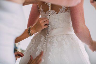 het trouwkleed van de bruid wordt dichtgeknoopt